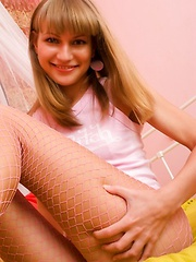 Teen with pretty bangs and a super sweet smile poses in pink fishnet pantyhose