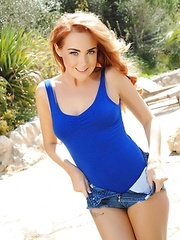 Tight blue bodysuit looks good on the sexy redhead stripping outdoors